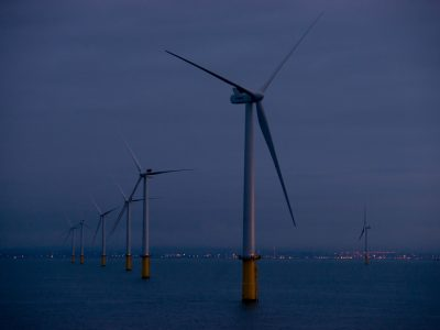 Wind farm at dusk with coastal lights in the background